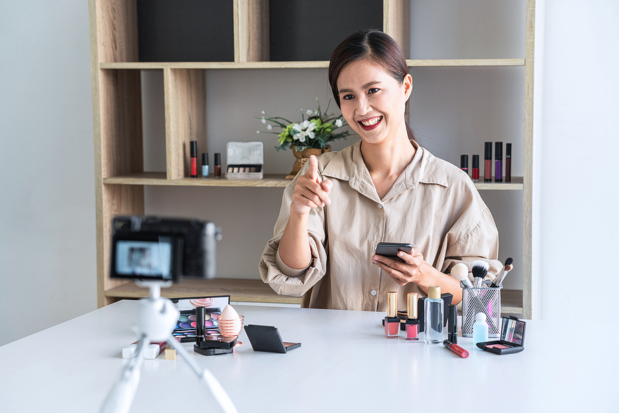 Happy smiling elegant woman blogger is showing present make up tutorial beauty cosmetic review product and broadcast live streaming video blogging to social network teaching online on camera screen.